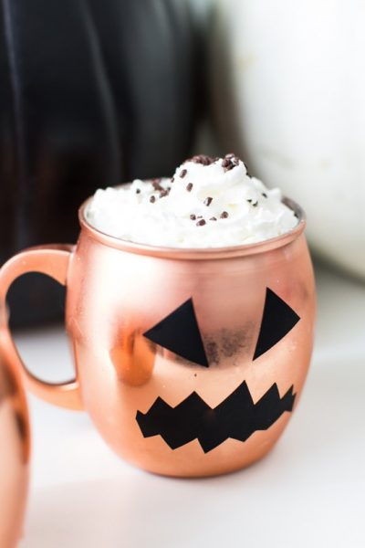 photo of a copper mug with pumpkin face decal and whipped cream