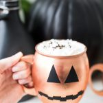 photo of a hand holding a copper mug with pumpkin face on it