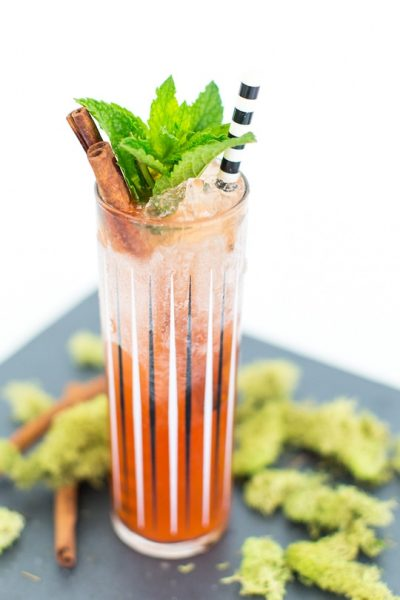 a zombie cocktail glass with cocktail and cinnamon sprig