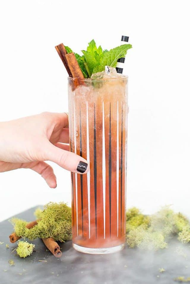 a hand holding a zombie glass with garnishes