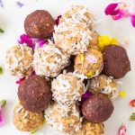 a mound of peanut butter balls with coconut flakes, cinnamon, and edible flowers