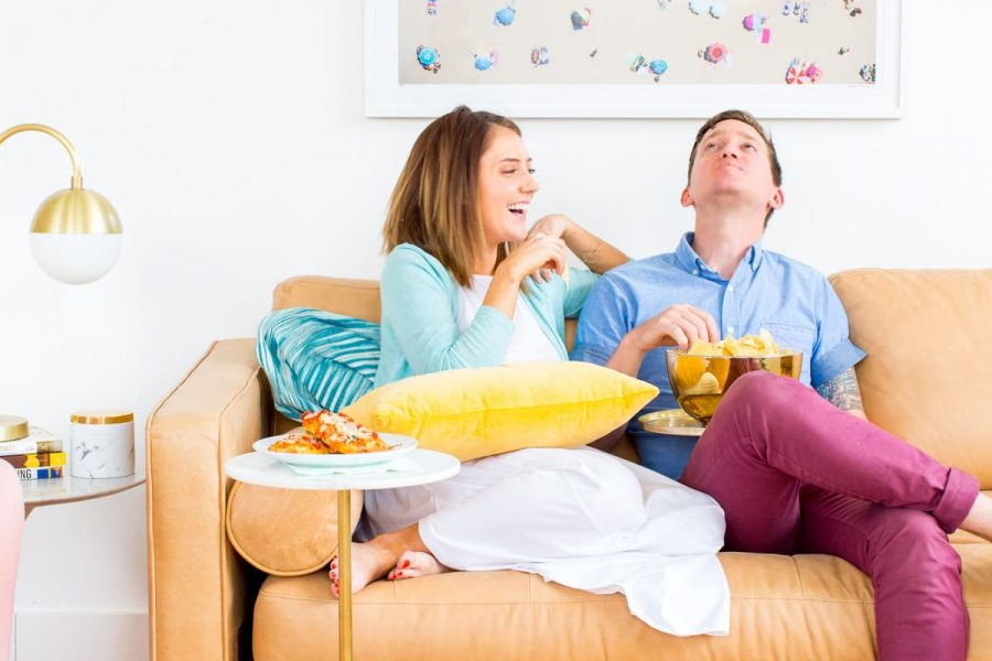 photo of a couple on a couch next to a DIY c table with pizza by sugar and cloth