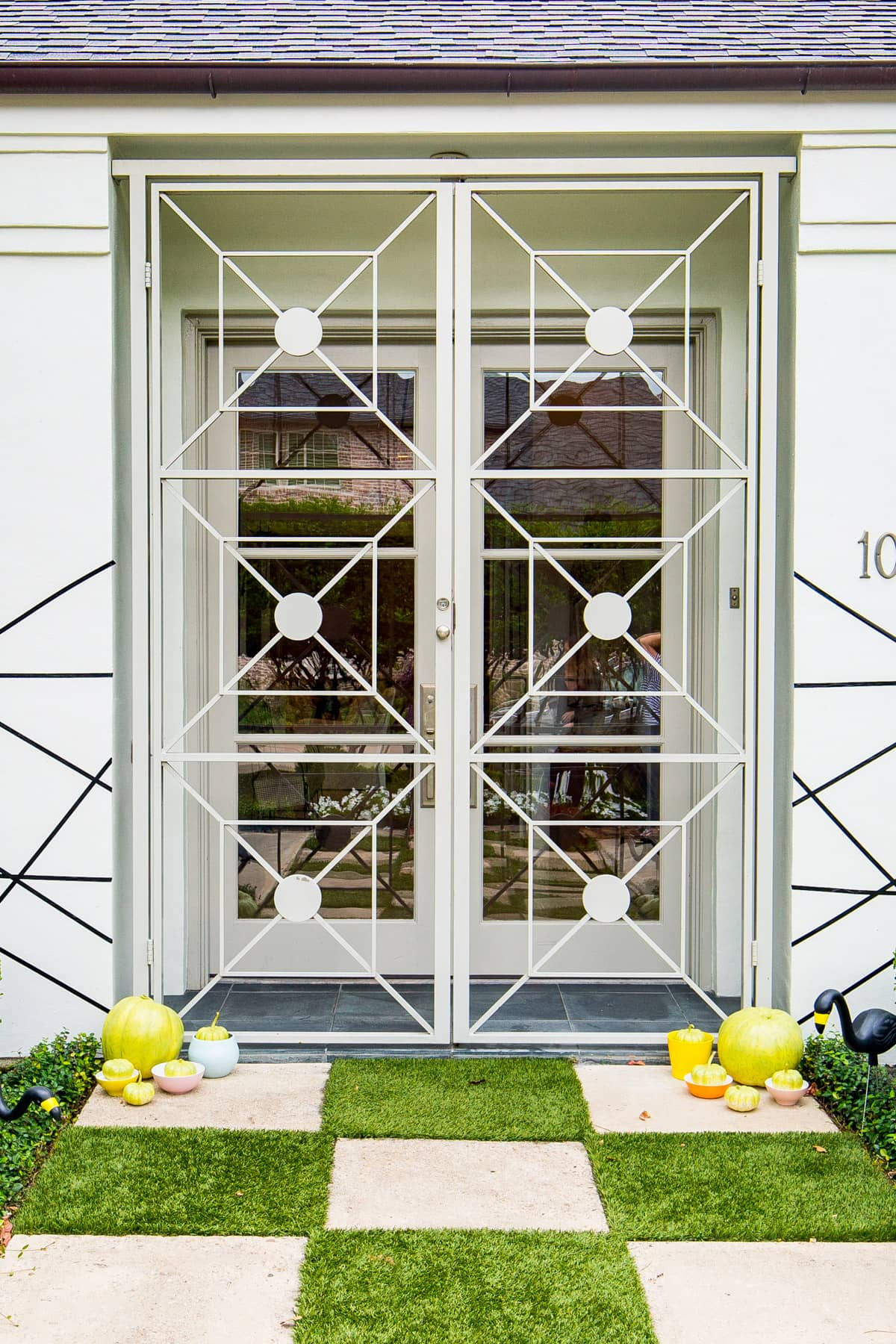 mid century metal doors and a checkered entrance! - Palm Springs Inspired Halloween Entryway Decor & Product Round Up by top Houston lifestyle blogger Ashley Rose - #halloweendecor #halloween #decor #home #holidays #curbappeal #palmsprings #midcentury