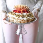 vertical photo of a girl holding a chai crepe cake on a cake stand by sugar and cloth