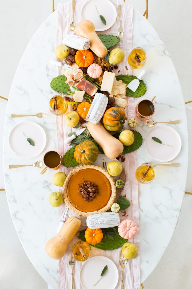 overhead photo of a styled thanksgiving table centerpiece decor with gourds by sugar and cloth