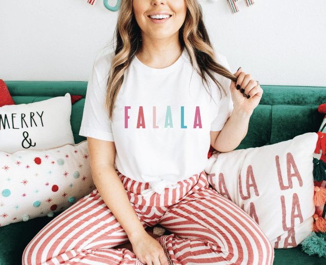 girl on a sofa wearing a falalala holiday shirt with striped pants