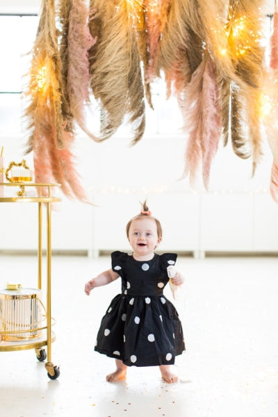 gwen standing in the photobooth - Sharing photos via Live Albums and google hub! Pampas Grass DIY Photo Backdrop by top Houston lifestyle blogger Ashley Rose of Sugar & Cloth #diy #nye #backdrop #photography #photos #google #holidays #howto #weddings #parties #entertaining
