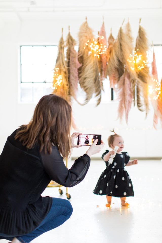 Snapping photos of the photobooth - Sharing photos via Live Albums and google hub! Pampas Grass DIY Photo Backdrop by top Houston lifestyle blogger Ashley Rose of Sugar & Cloth #diy #nye #backdrop #photography #photos #google #holidays #howto #weddings #parties #entertaining