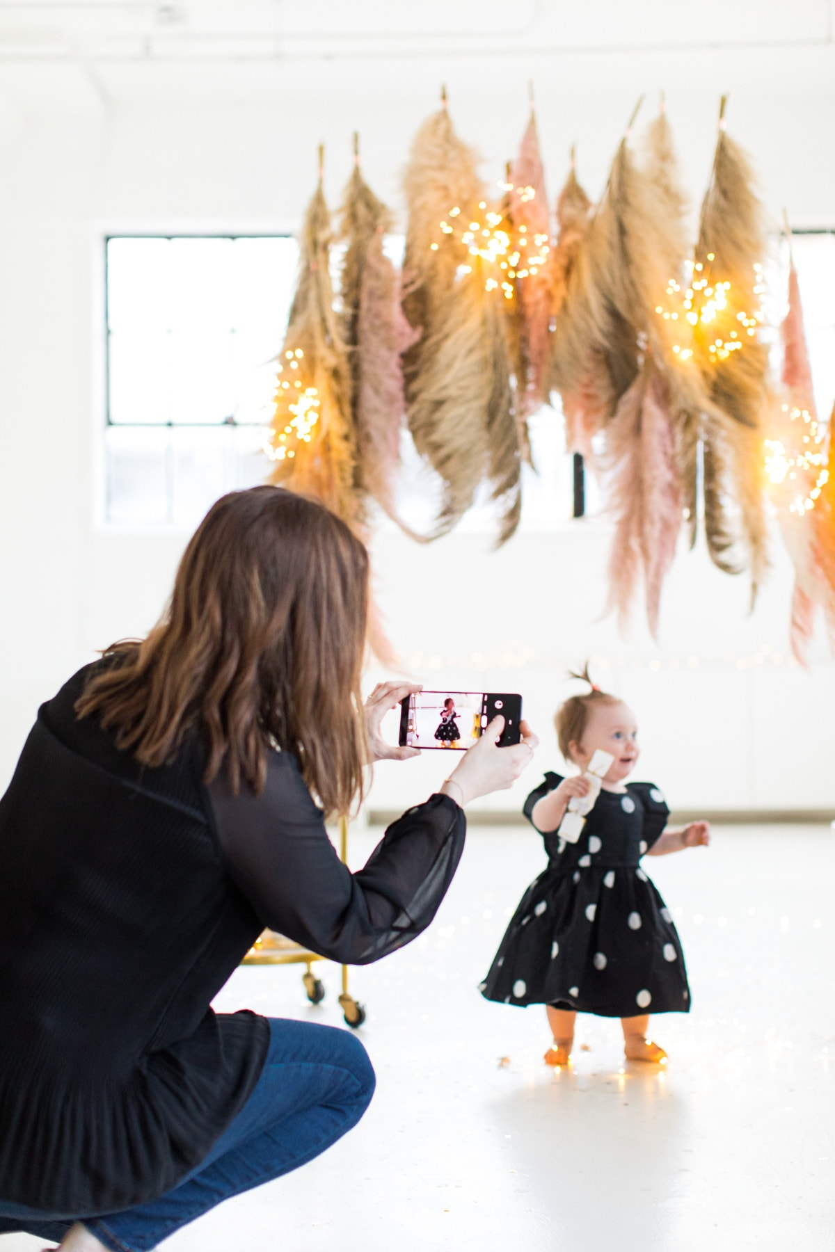 Snapping photos of the photobooth - Sharing photos via Live Albums and google hub! Pampas Grass DIY Photo Backdrop by top Houston lifestyle blogger Ashley Rose of Sugar & Cloth #diy #nye #backdrop #photography #photos #google #holidays #howto #weddings #parties #entertaining