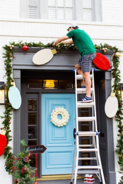 installing the decor! Jumbo Lights Outdoor DIY Christmas Decorations! by top Houston lifestyle blogger Ashley Rose of Sugar & Cloth #DIY #howto #christmas #holidays #decorations #decor #home #frontdoor #entrance