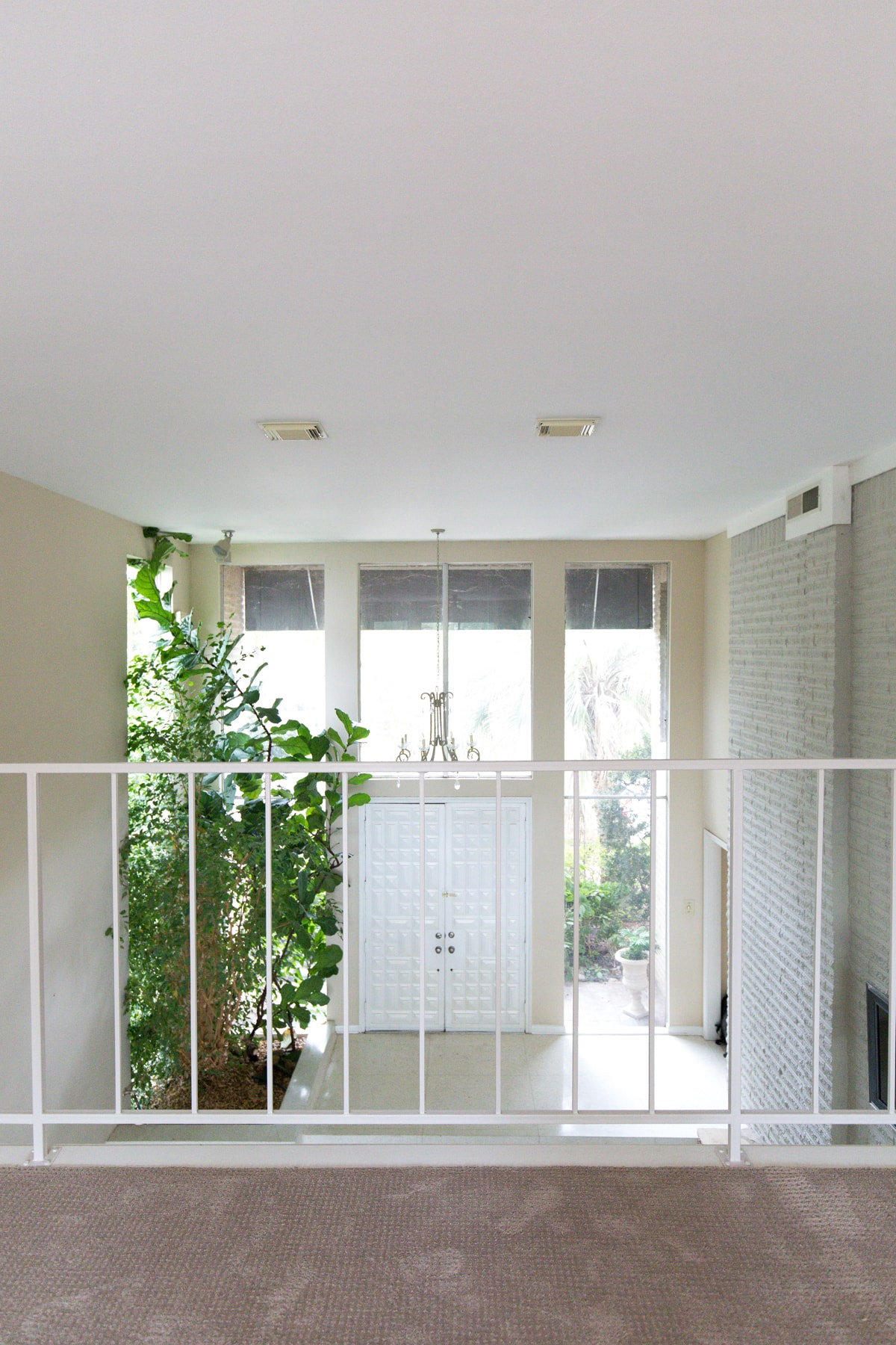 the view into the living room from the balcony upstairs - One Room Challenge Week 1: The Before Photos of Our Living Room + Dining Room by top Houston lifestyle blogger Ashley Rose of Sugar and Cloth #decor #homedecor #diy #interiors #renovations