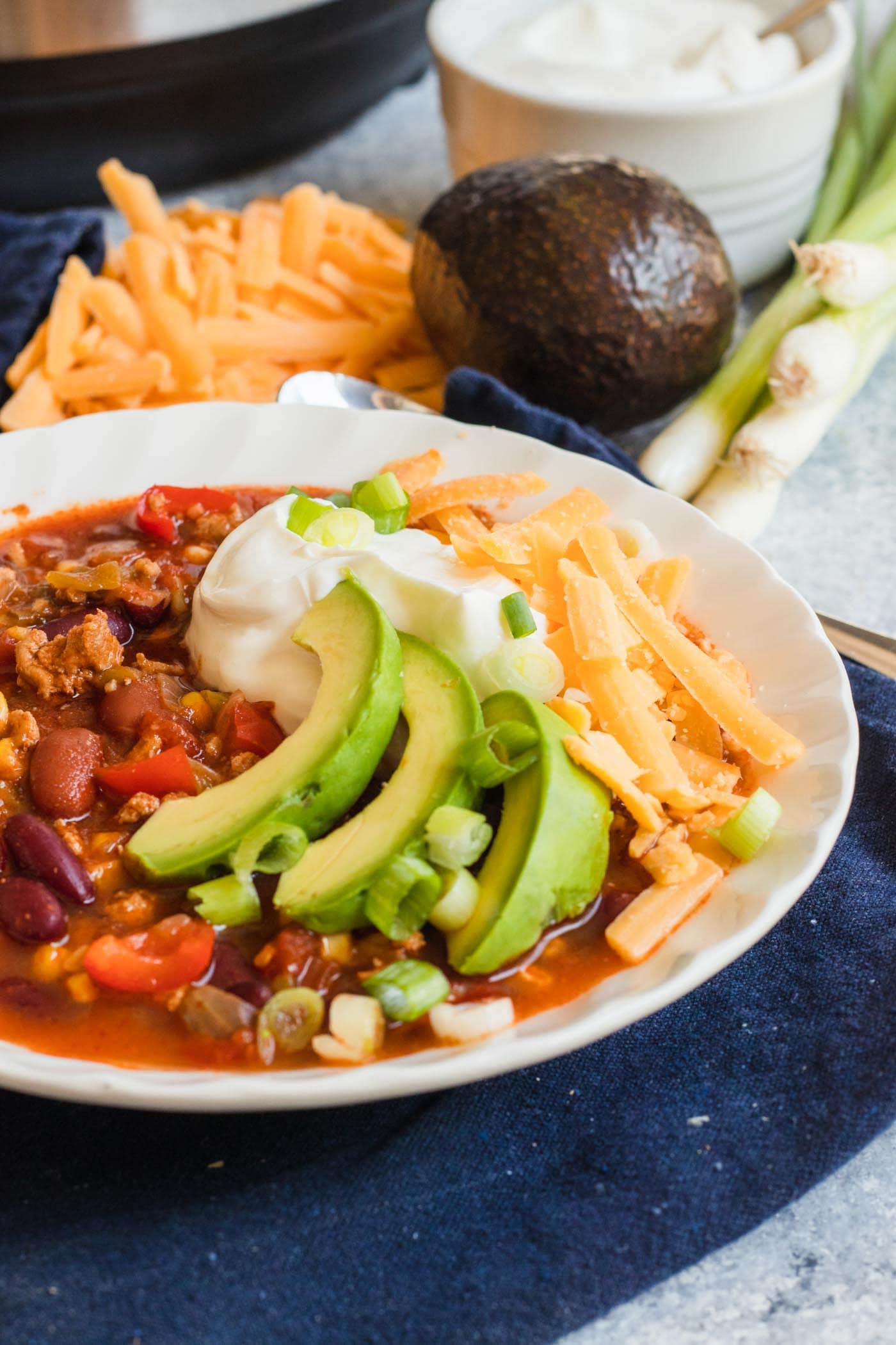 photo of the Best Easy Turkey Chili Recipe garnished with avocado, cheese and sour cream by top Houston lifestyle blogger Ashley Rose of Sugar & Cloth