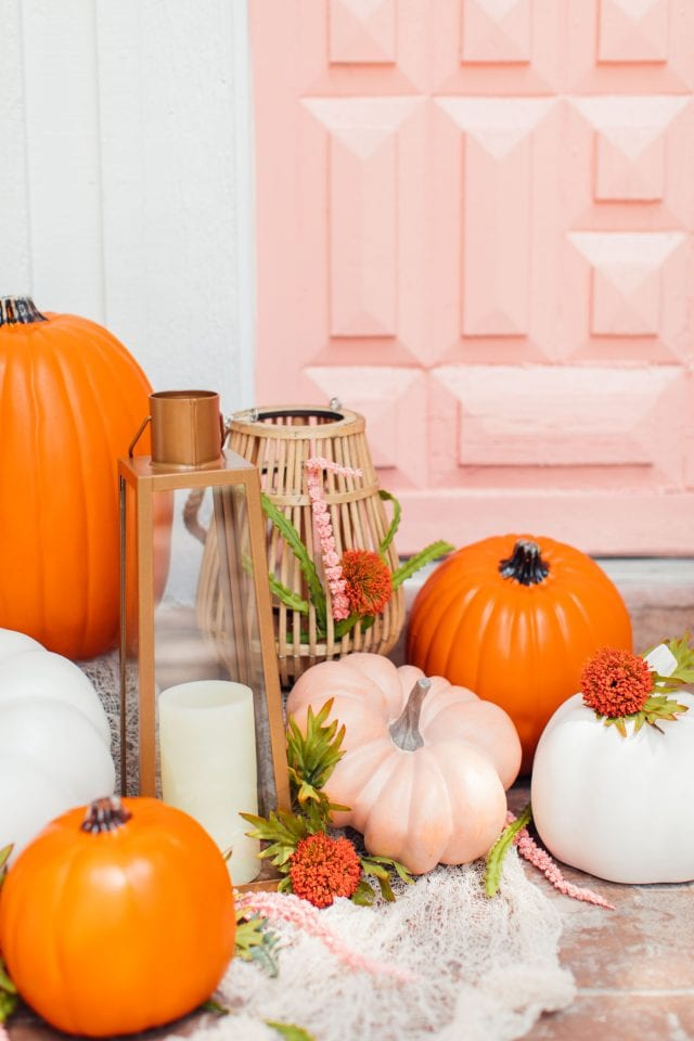 photo of pumpkins in front of a pink door