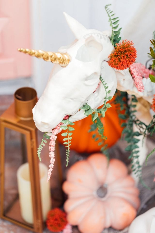 close up photo of a gold unicorn skeleton outdoor halloween decoration