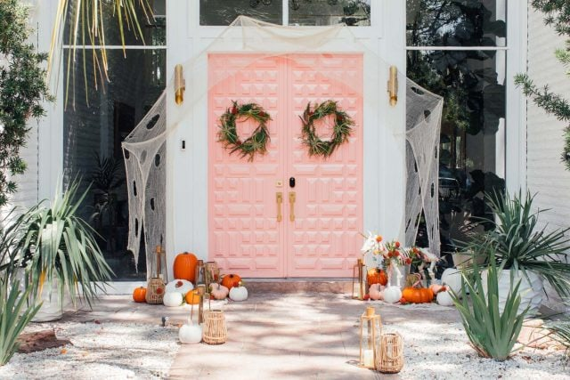 horizontal photo of a pink front door with halloween decorations
