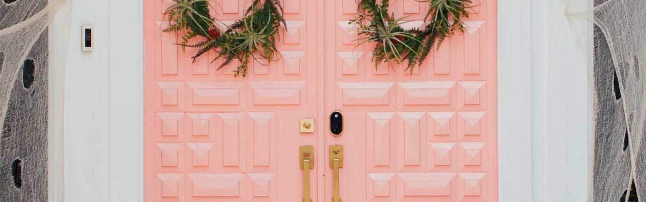 photo of a pink front door with halloween door decor