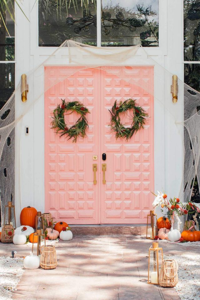 photo of a pink front door with halloween door decor