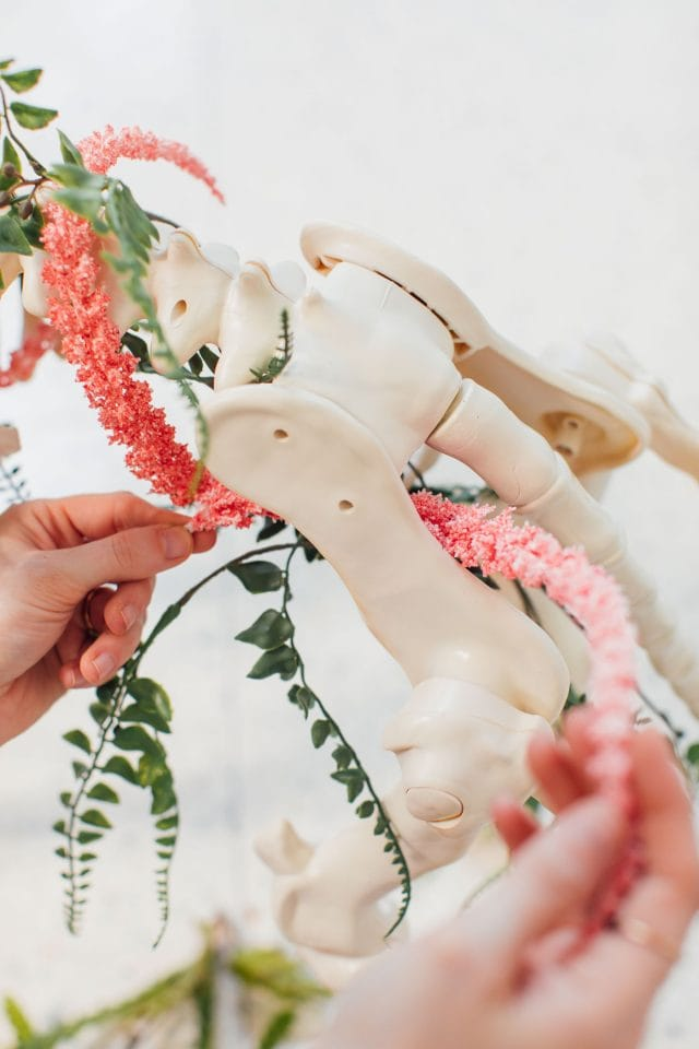 photo of stringing fake flowers onto a unicorn skeleton