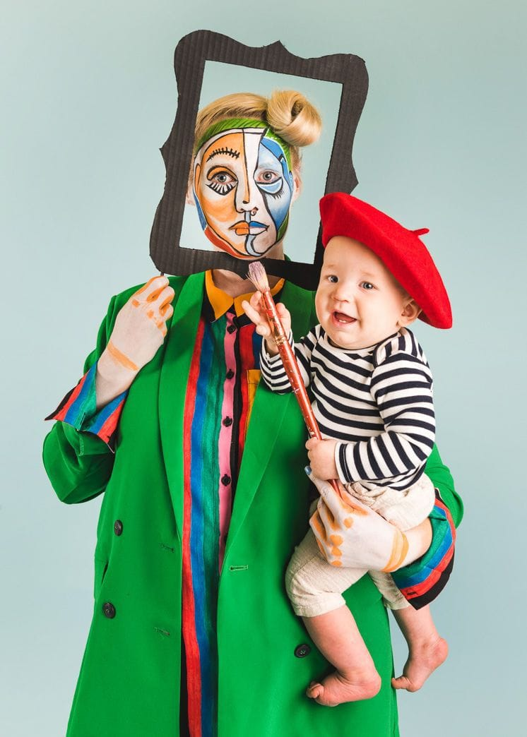 Photo of mother holding young child dressed as Picasso. Mother is dressed as a masterpiece.