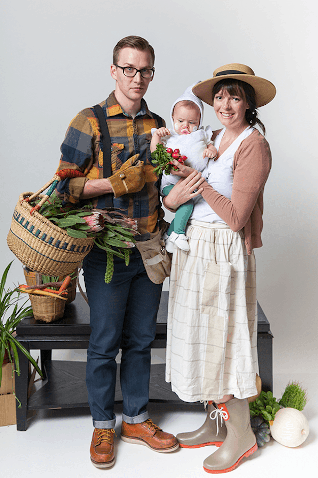 Photo of parents in gardener costumes holding baby in garlic costume