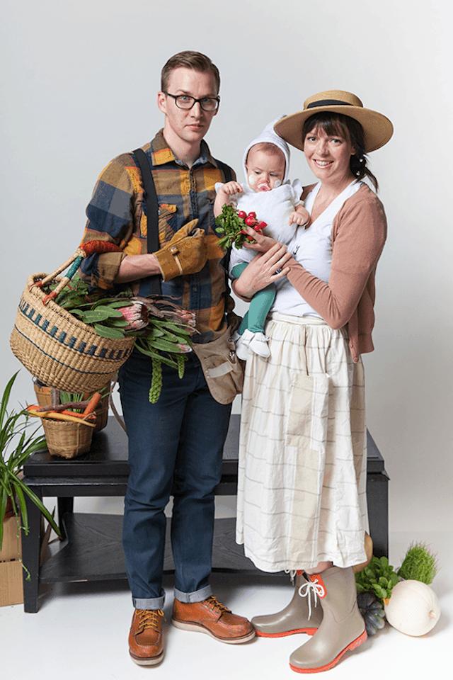 Photo of parents in gardener costumes holding baby in garlic costume