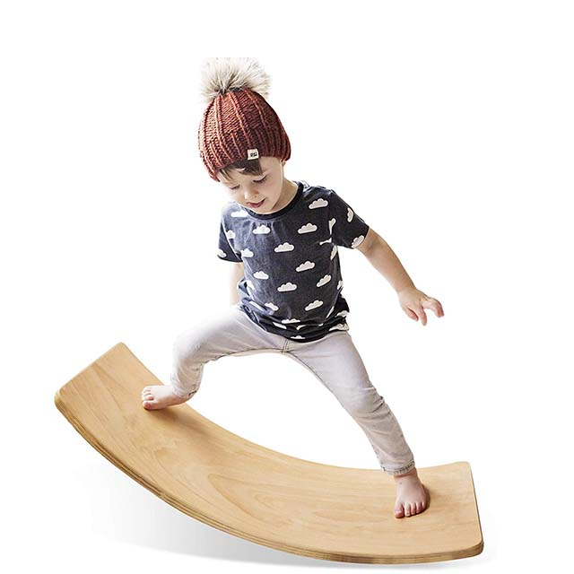 photo of a young boy playing on a wooden wobble balance board