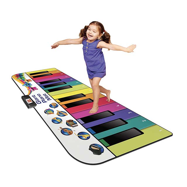photo of a little girl jumping on a large floor keyboard