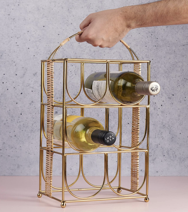 a hand holding a gold wine rack caddy with bottles In it