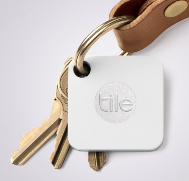 a set of gold keychains and leather keychain with a tile mate gift