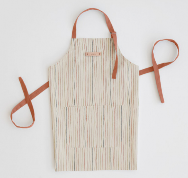 a striped apron laying flat with a personal name tag