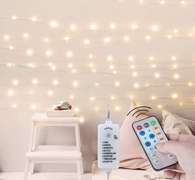 remote controlled string lights on a wall of a girls room with hand
