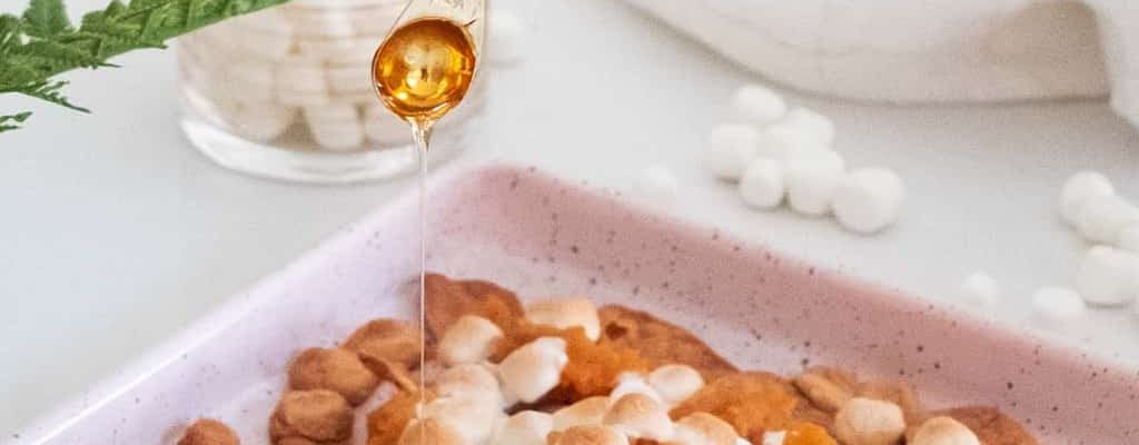 photo of honey being drizzled on the Easy Snack Ideas Sweet Potato Crackers Recipe by top Houston lifestyle blogger Ashley Rose of Sugar & Cloth