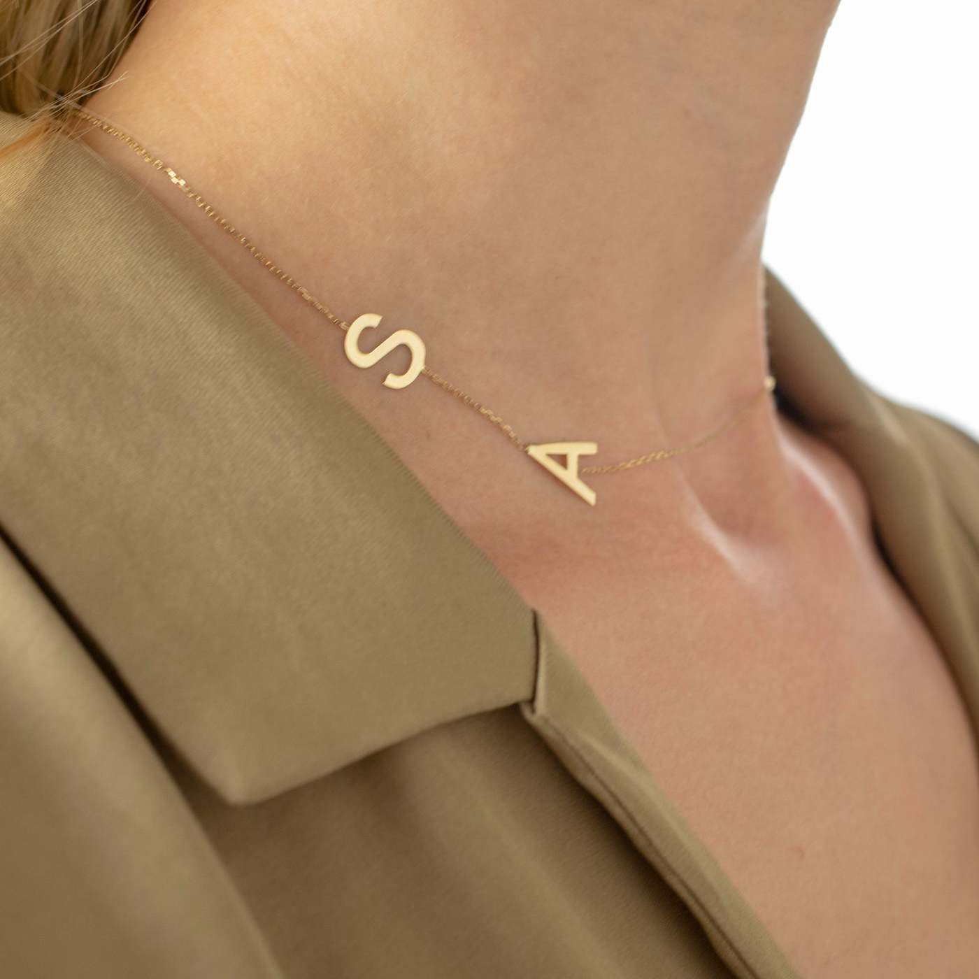 close up of woman wearing a gold initial necklace