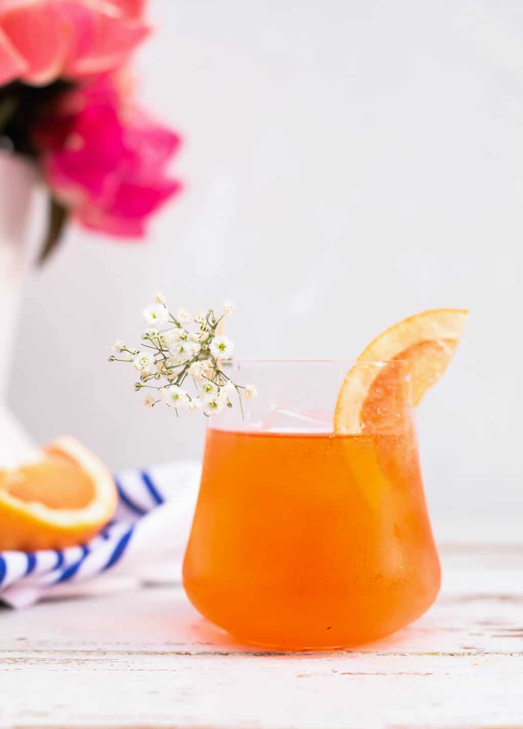 photo of a grapefruit slice and baby's breath as garnishes for an Elderflower Aperol Spritz by top Houston lifestyle blogger Ashley Rose of Sugar & Cloth