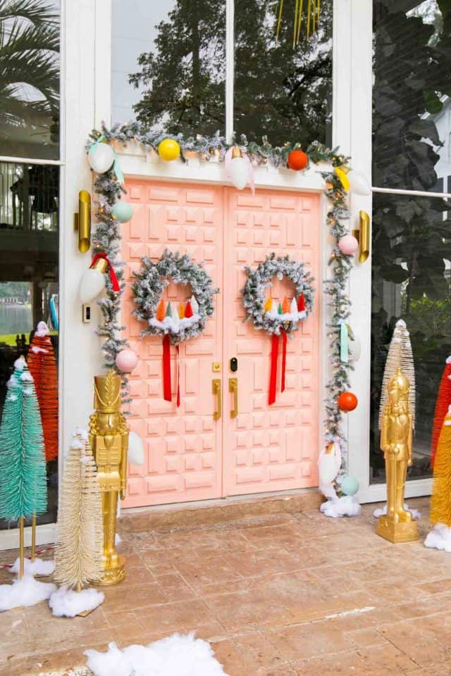 side angle view of a pink door with christmas decor