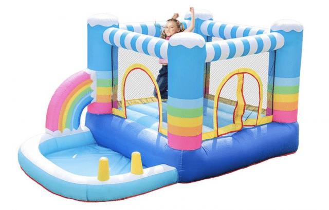 a rainbow themed bounce house with girl jumping
