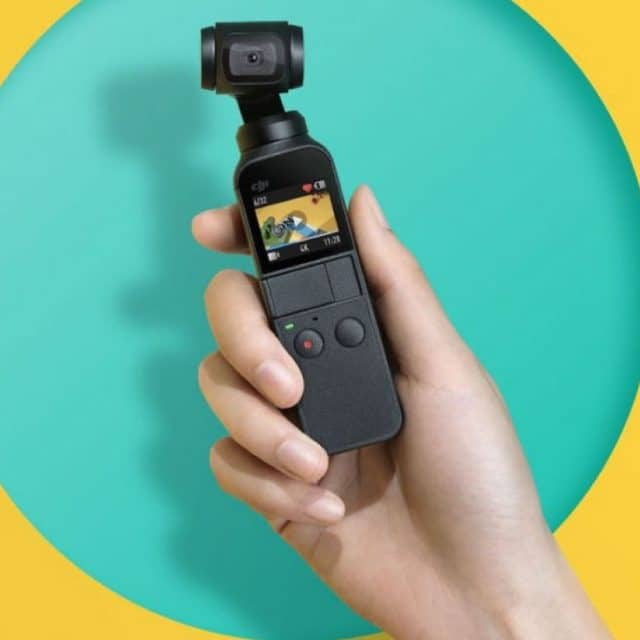 a womens hand holding a DJI osmo camera in front of a blue background