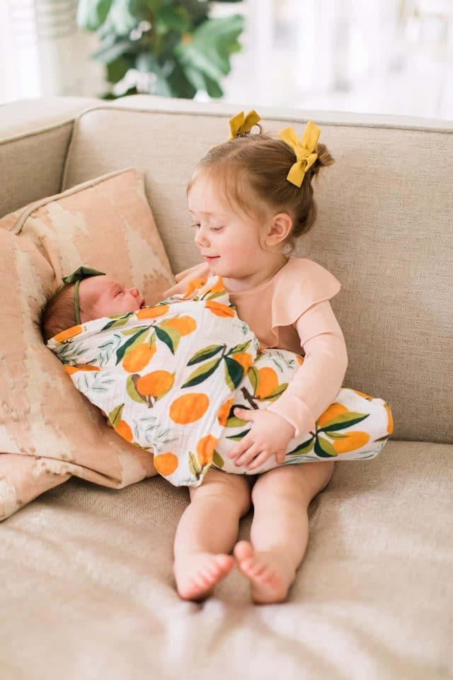 toddler girl holding new baby sister