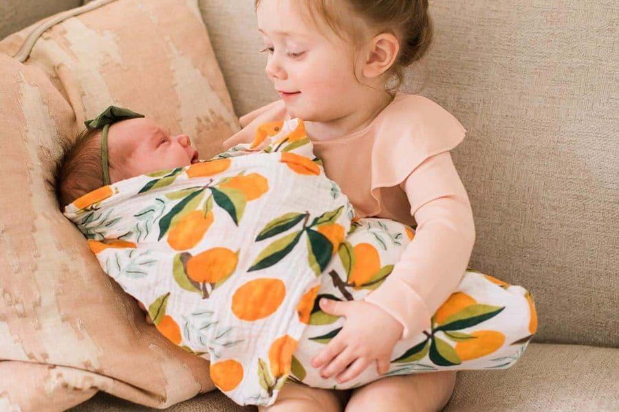 toddler girl holding new baby sister