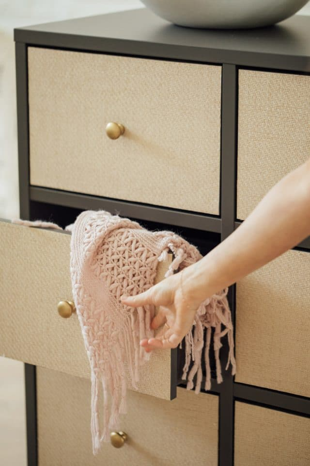 pink throw blanket coming from a rattan drawer
