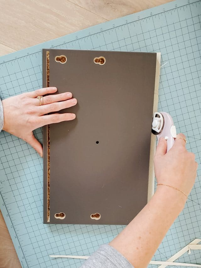 using a rotary cutter on a cutting board with drawers