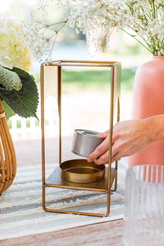 a hand placing a gel can on a gold lantern to show how to keep flies away outside