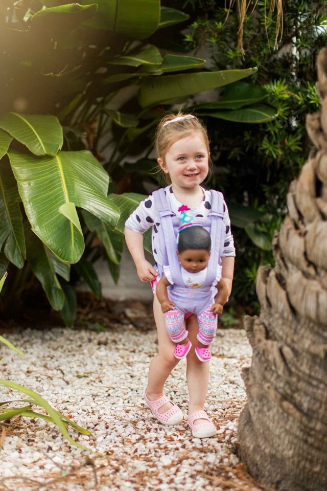 toddler girl and baby doll carrier