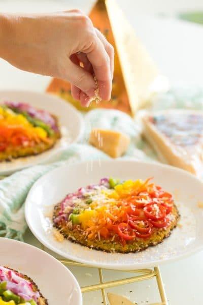 a hand sprinking stella asiago cheese onto a veggie pizza