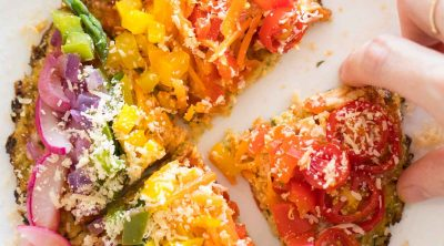 overhead view of a rainbow veggie topped pizza with cauliflower pizza dough and a hand