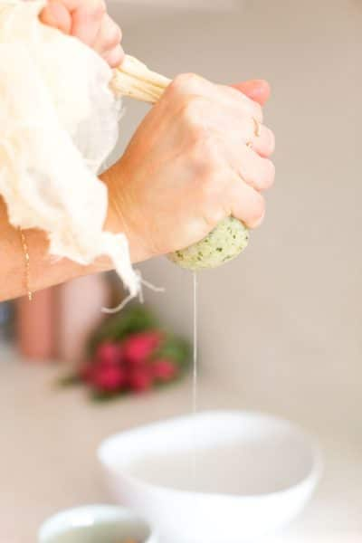 hands ringing out cauliflower florets from cheese cloth