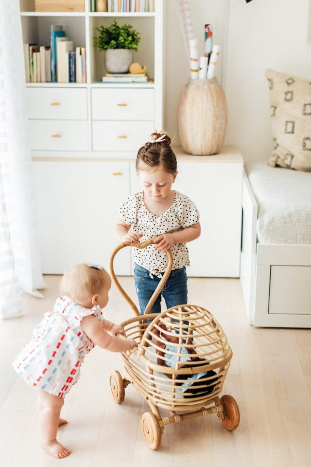 little girls playing with a rattan doll cart