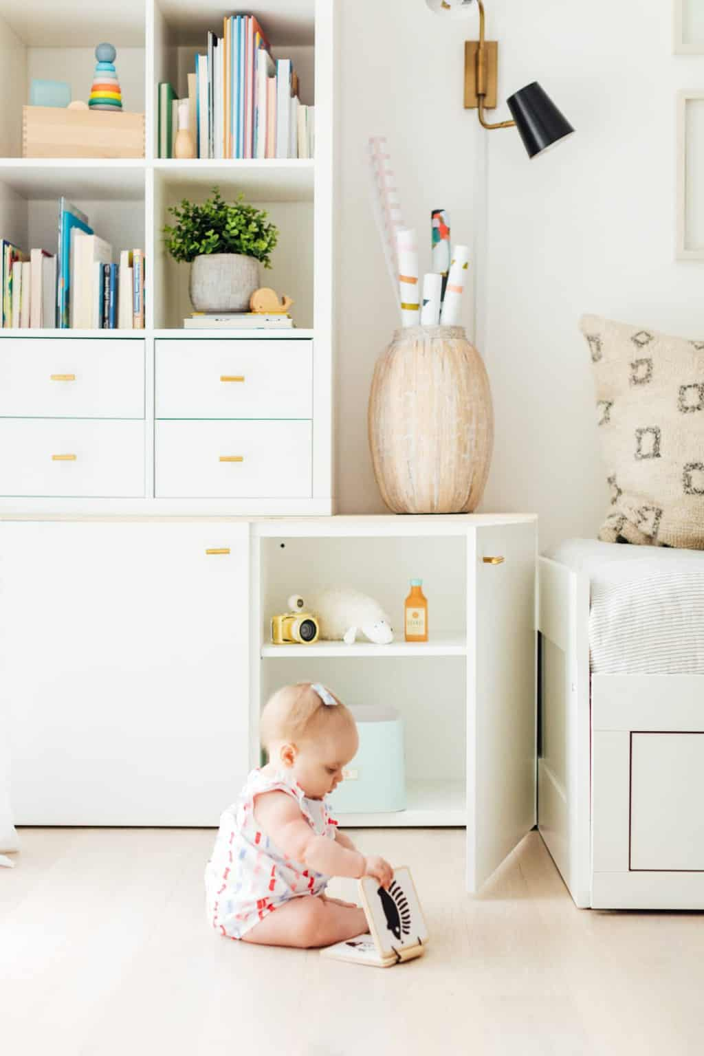 baby with a baby book in playroom