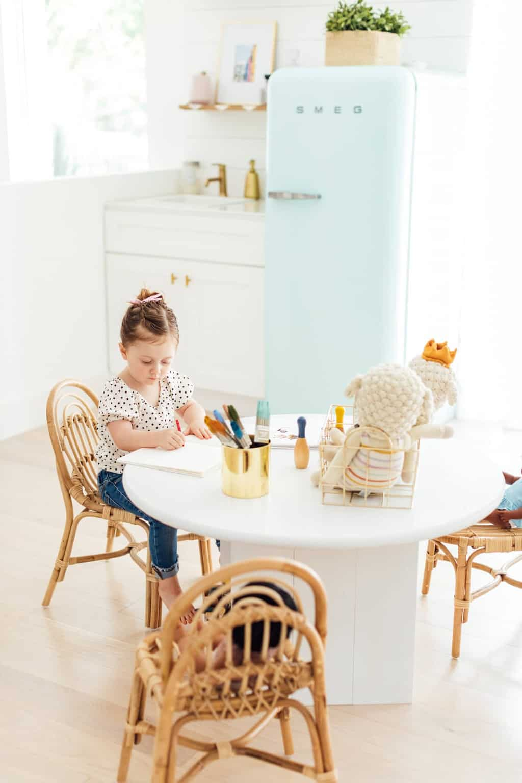 little girl at a DIY kids table in a playroom