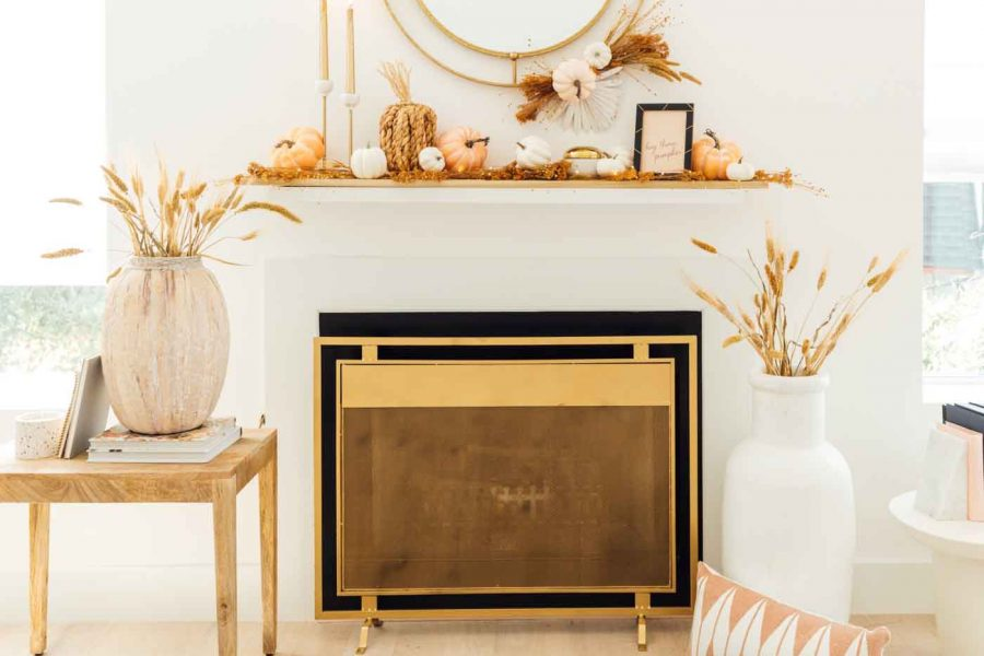 a fireplace with fall pumpkins and styling